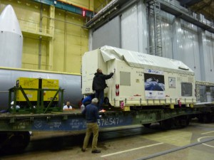 Unloading of spacecraft container in the MIK General Hall; payload fairing in the background